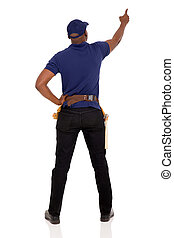 rear view of african handyman pointing at empty space