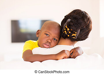 rear view of african woman holding her son