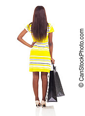 rear view of african woman holding shopping bags
