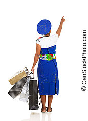 rear view of african woman pointing with shopping bags