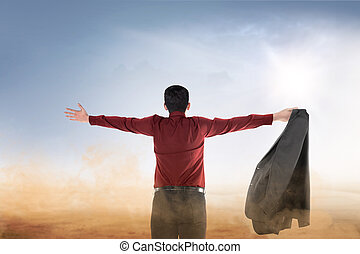 Rear view of asian businessman raised hands with open palm praying to god