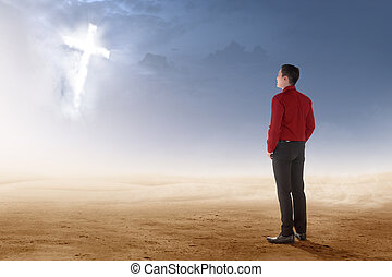 Rear view of asian businessman standing on desert and looking at glowing christian cross