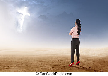 Rear view of asian businesswoman standing on desert and looking at glowing christian cross