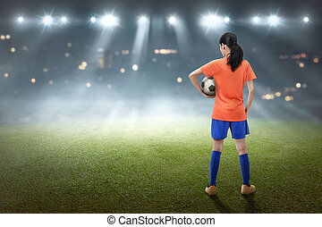 Rear view of asian female footballer with the ball