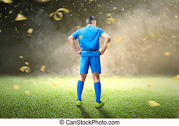 Rear view of Asian football player man in blue jersey standing with flying golden confetti
