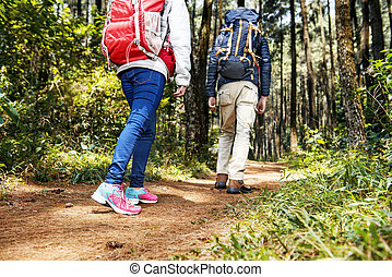 Rear view of asian hikers couple with backpack walking down