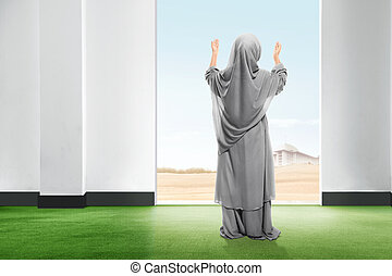 Rear view of asian little girl in veil standing on carpet raise the hand and gazing the sky from inside the room