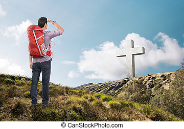Rear view of asian man with backpack looking at cross