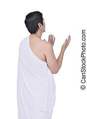 Rear view of asian muslim man in ihram cloth praying
