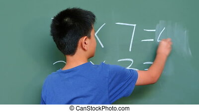 Rear view of Asian schoolboy solving math problem on ...