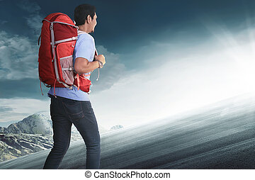 Rear view of asian tourist with backpack climbing