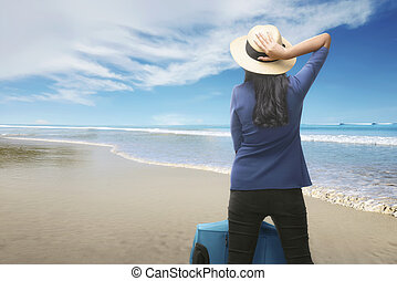 Rear view of asian traveler woman with suitcase relaxing