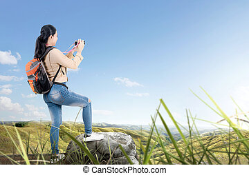 Rear view of Asian woman with a backpack holding a camera to take pictures
