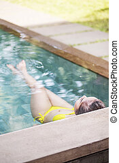 Rear view of asian woman with swimwear relaxing