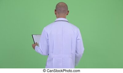 Rear view of bald multi ethnic man doctor thinking and reading on clipboard