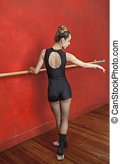 Rear View Of Ballerina Practicing At Barre In Studio - Full...