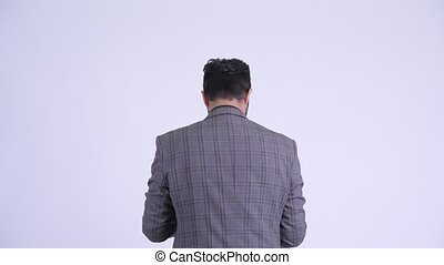 Rear view of bearded Persian businessman holding clipboard...
