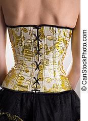 Rear view of beautiful woman in golden corset