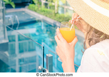 Rear view of beautiful woman in hat is drinking orange juice glass at poolside in summer.