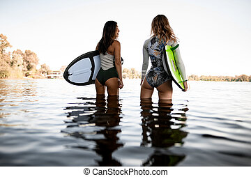 rear view of beautiful women standing in the water and holding surfboards in their hands