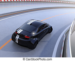 Rear view of black electric sports car driving on the...