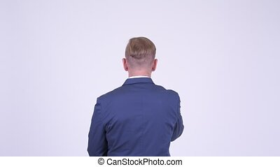 Rear view of blonde businessman pointing finger and...