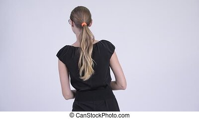 Rear view of blonde businesswoman waiting and thinking