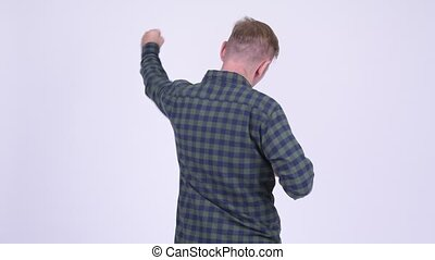 Rear view of blonde hipster man excited with arms raised