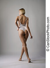 Rear view of blonde posing in sexy white bodysuit