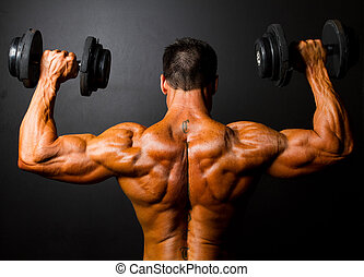 bodybuilder training with dumbbells - rear view of...