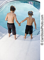 Rear view of boys looking in swimming pool