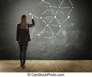 Rear View of Brunette Business Woman Drawing Connected Lines on Chalkboard in Connectivity, Communication and Network Concept Image