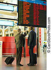 business partners checking flight information at airport