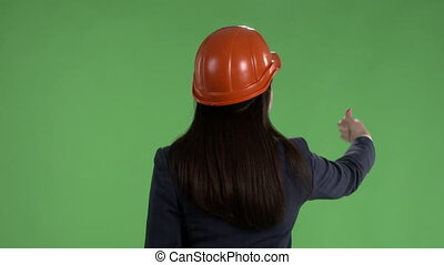 Rear view of business woman in hard hat points to something against green screen