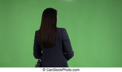 Rear view of business woman meets someone looking at watch against green screen