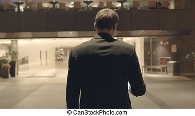 Rear view of businessman near the reception. Stock. There...