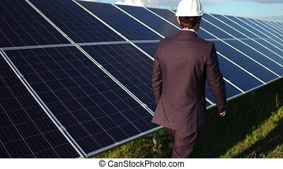 Rear view of businessman walking at solar energy station....