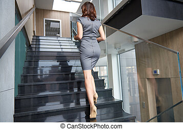 Rear view of businesswoman on steps