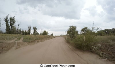 Rear view of car driving along a rural dirt road
