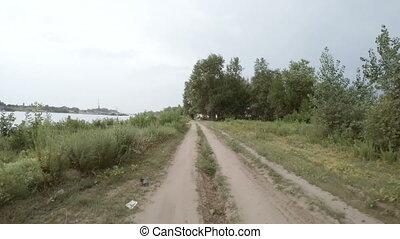 Rear view of car driving along a rural dirt road