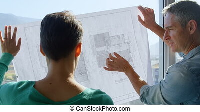 Rear view of Caucasian Business people discussing over blueprint in the office 4k