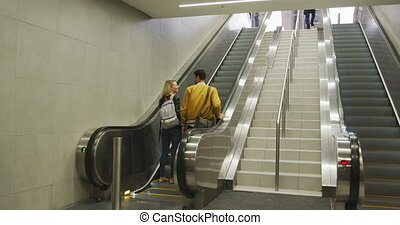 Rear view of a Caucasian couple wearing casual clothes, leaving a metro station, standing on escalator, smiling and talking.