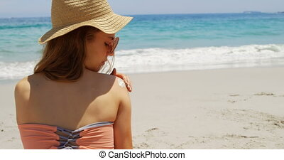 Rear view of Caucasian woman applying lotion on her body at beach 4k