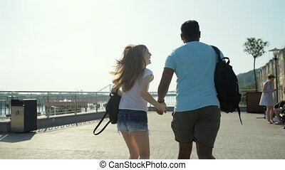 Rear view of cheerful couple running and holding hands -...
