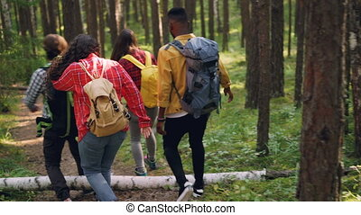 Rear view of cheerful young men and women tourists with knapsacks trekking in woods along wild path, enjoying beautiful nature and talking. People and forest concept.