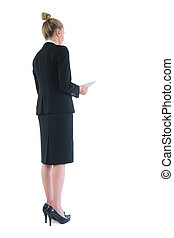 Rear view of chic young businesswoman holding her tablet