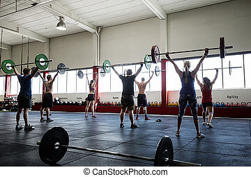 Rear View Of Clients Lifting Barbells In Gym