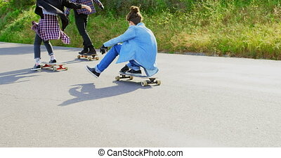Rear view of cool young caucasian skateboarders skating on downhill at countryside 4k