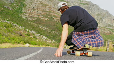 Rear view of cool young man riding on skateboard on downhill at countryside road 4k