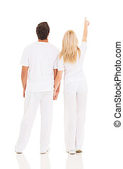 rear view of couple pointing up isolated on white background